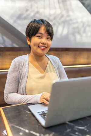 Portrait of Asian woman in short hair working on laptop Stok Fotoğraf