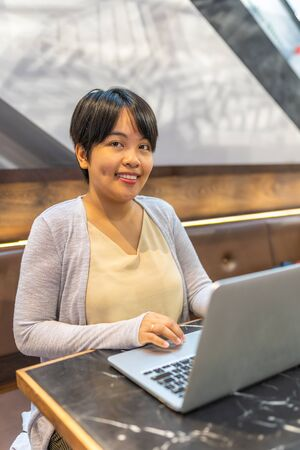 Smiling Asian short hair woman working with laptop Stok Fotoğraf