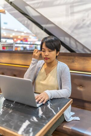 Short hair Asian woman working on laptop on coffee table Banco de Imagens