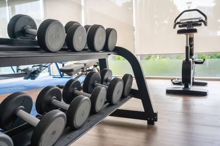 Fitness machine and dumbbells on shelf in gym room