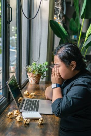 Frustrated Asian lesbian sitting with laptop and crumpled paper balls Stok Fotoğraf