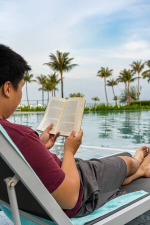 Asian man relaxing with a book at beautiful swimming pool Stok Fotoğraf