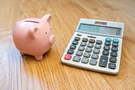 Cute Piggybank and calculator on wooden background