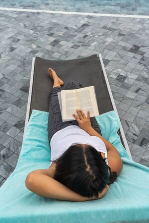 High angle view of woman reading book on summer vacation Stok Fotoğraf