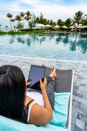 Woman using tablet while enjoying summer vacation at swimming pool Imagens