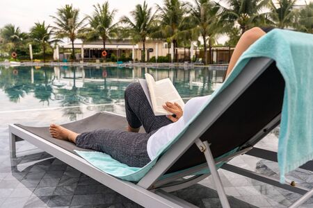 Asian woman relaxing and reading book at the swimming pool Stok Fotoğraf