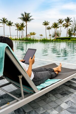 Closeup of Asian woman holding tablet at beautiful swimming pool