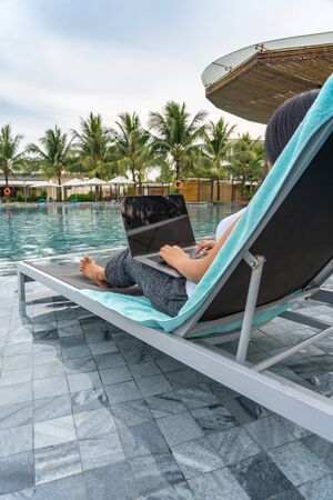Asian woman using laptop on a bench at swimming pool Stok Fotoğraf