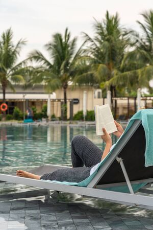 Woman hand holding book while reading at swimming pool