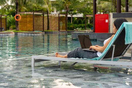 Asian woman sitting at nice swimming pool and using laptop