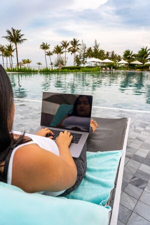 Woman using laptop while sitting on bench at swimming pool Stok Fotoğraf