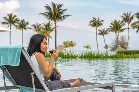 Asian woman enjoying red wine at beautiful tropical swimming pool