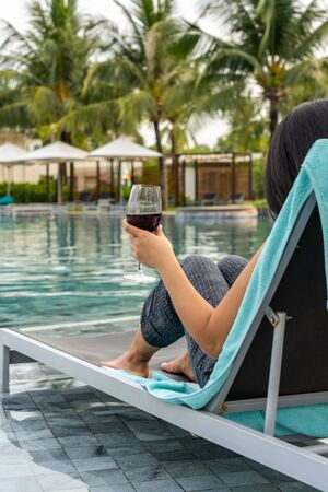 Woman hand holding glass of wine at swimming pool