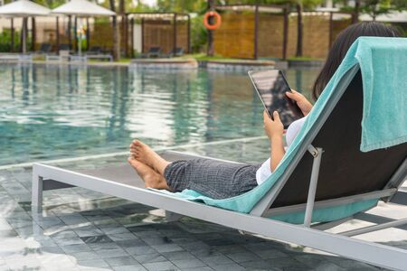 Young woman relaxing and using tablet at swimming pool Stok Fotoğraf