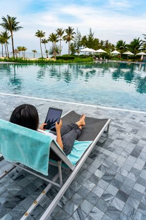 Woman enjoy summer vacation and using tablet at swimming pool Stok Fotoğraf