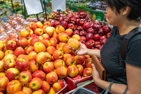 Young Asian woman buying apple at fruit stand in supermarket