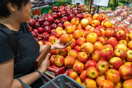 Asian woman picking apple at fruit stand in grocery store Stok Fotoğraf