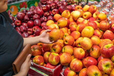 Asian woman buying and choosing red apple at fruit stand Stok Fotoğraf