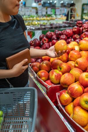 Asian woman buying apple at fruit stand in supermarket
