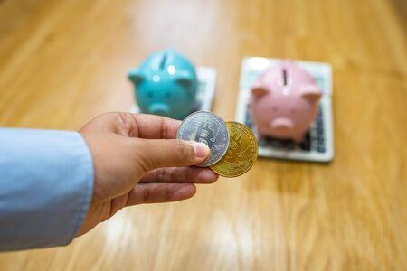 Businesswoman hand holding bitcoin with piggy bank and calculator background Zdjęcie Seryjne