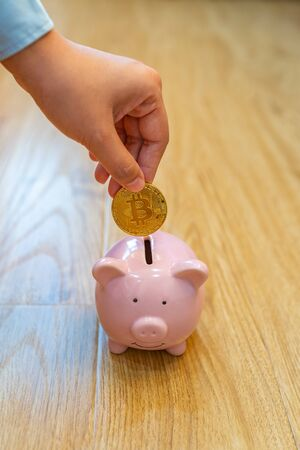Close up of human hand inserting golden bitcoin into piggybank