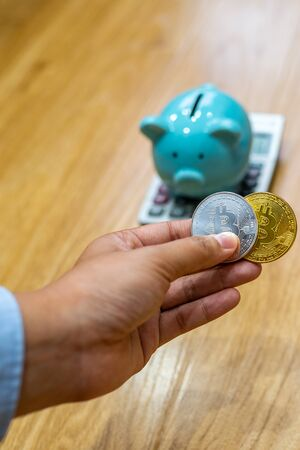 Businesswoman hand holding bitcoin and put into piggy bank