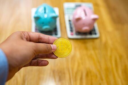 Close up of businesswoman hand holding bitcoin with piggybank behind Zdjęcie Seryjne