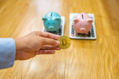 Businesswoman hand holding bitcoin with piggybank and calculator background
