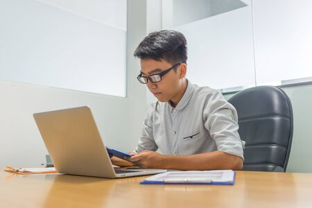 Young Asian businessman reading report in the office