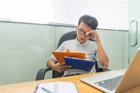 Tired businessman reading financial data on document