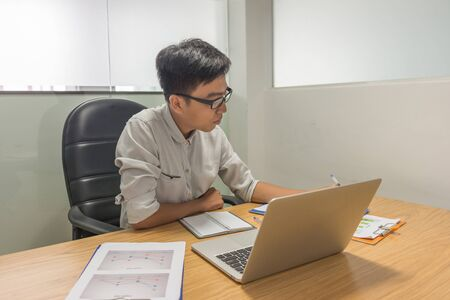 Young Asian supervisor working on laptop and statistic documents
