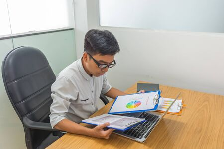Asian businessman reading document report in the office