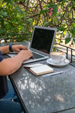 Woman hand working on laptop outdoor the coffee shop Фото со стока