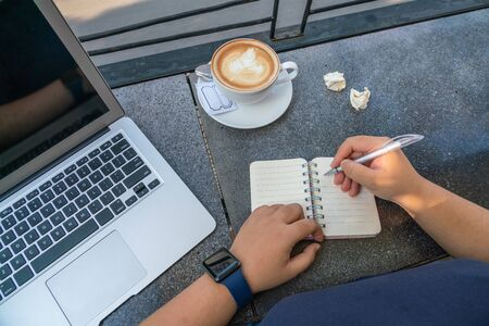 High angle view of human hand writing notebook beside laptop