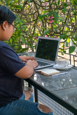 Asian freelancer working on laptop at outdoor coffee bar