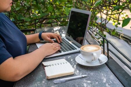 Freelancer using laptop next to notebook and cup of cappuccino Stok Fotoğraf