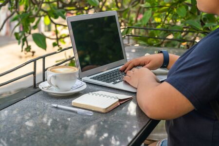 Freelancer working on laptop at coffee table outdoor Stok Fotoğraf