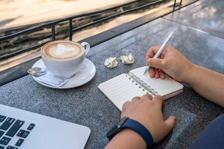 Woman holding pen and writing notes outdoor