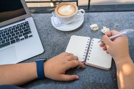 Woman hand holding pen and writing notebook beside laptop