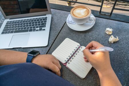 Human hand writing notebook at coffee table