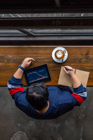 Vertical photo of Asian investor tracking stock market on tablet Stok Fotoğraf