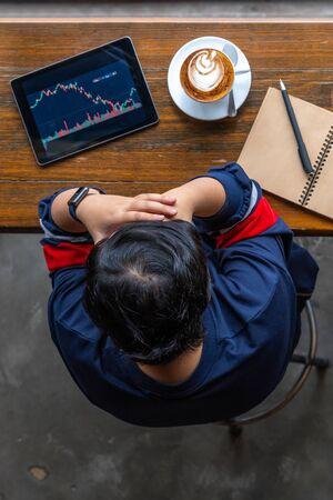 Young Asian investor having headache while watching stock trading graph Stok Fotoğraf