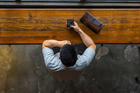 Top view of muscled Asian man using cellphone and tablet Stock Photo