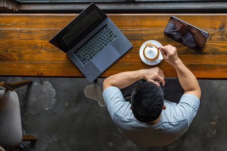 Asian freelancer working with laptop and enjoying hot cappuccino