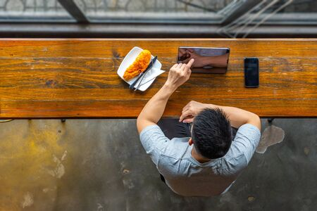 High angle view of freelancer using tablet and having breakfast