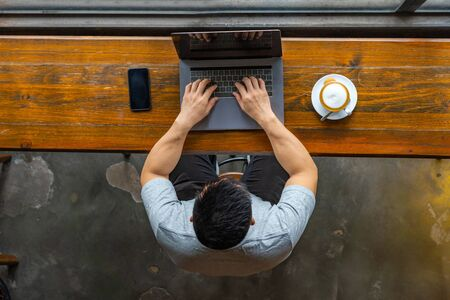 Isolated Asian freelancer working on laptop at rustic coffeeshop Stock Photo