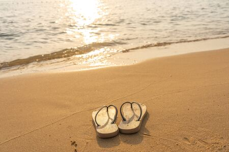 Pair of slipper on the peaceful beach in sunset