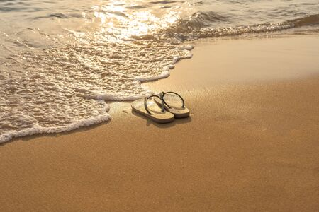 Slipper on beautiful beach in the sunset Imagens