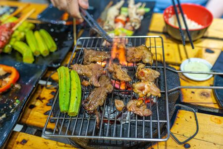 Barbecue meat and lady finger vegetables on flaming charcoal stove