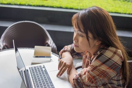 Asian woman using laptop touchpad on coffee table